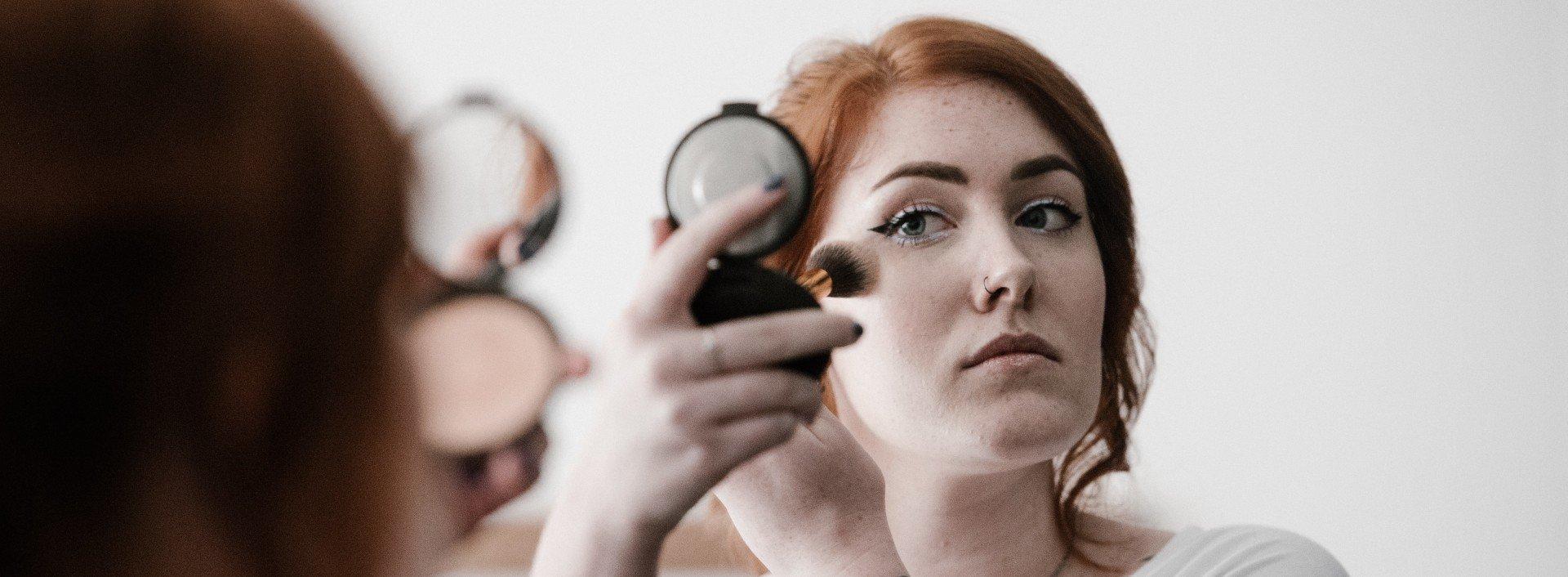 Make-up-Vokabular: Eine Frau trägt Make-up auf, während sie in einen Handspiegel schaut.