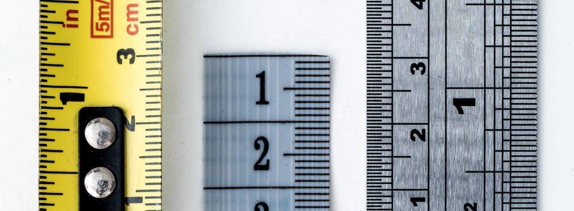 Drei Lineale liegen nebeneinander auf einem weißen Hintergrund und zeigen die Maße in englischer Sprache.