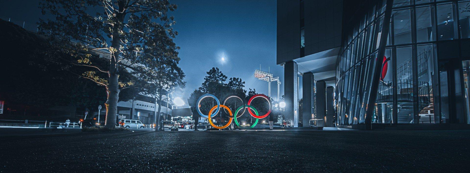 Englische Vokabeln für die Olympischen Spiele: Die olympischen Ringe sind in einer dunklen Straße bei Nacht abgebildet.