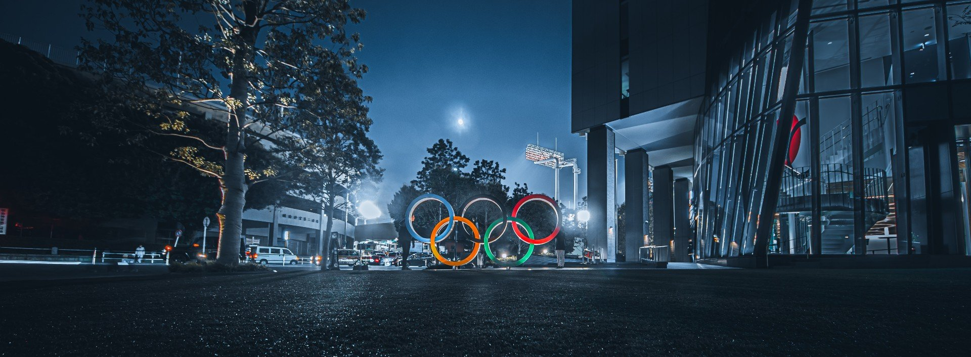 Olympic Vocabulary: the Olympic rings are pictured in a dark street at night.