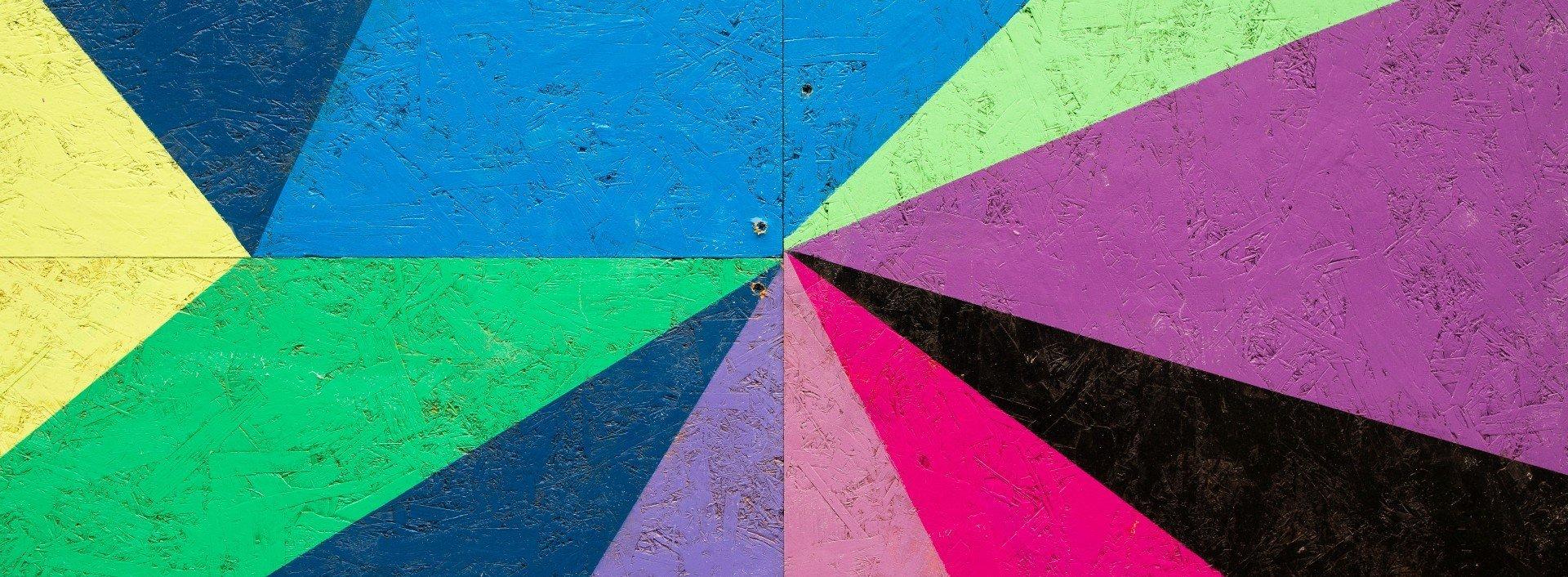 Formen auf Englisch: Viele verschiedene farbige Formen bilden ein Bild an der Wand.