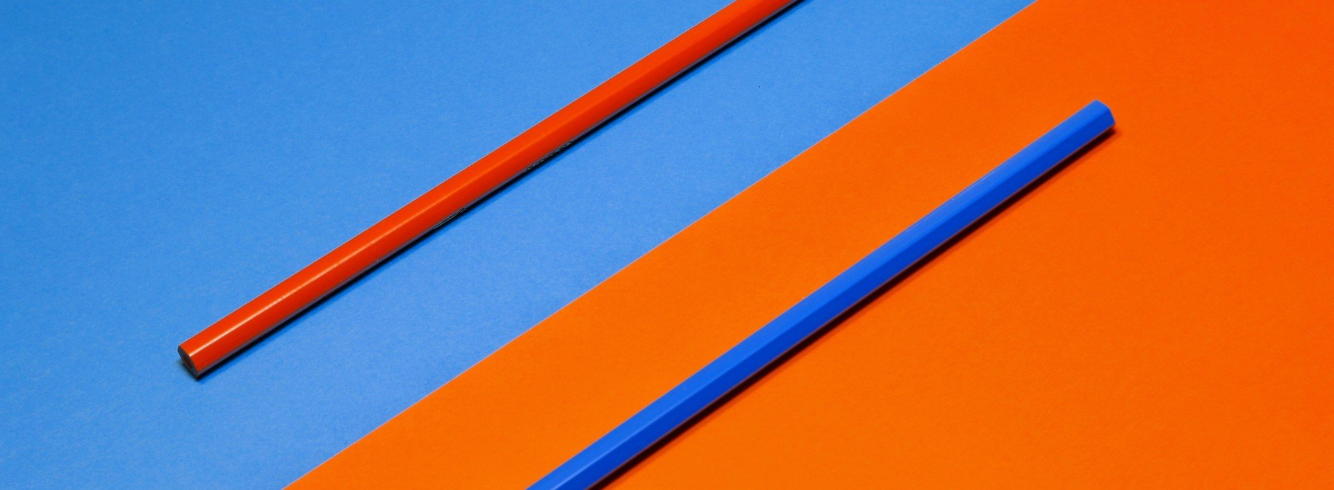 Opposites in English: blue and orange colored pencils are shown on blue and orange color fields.