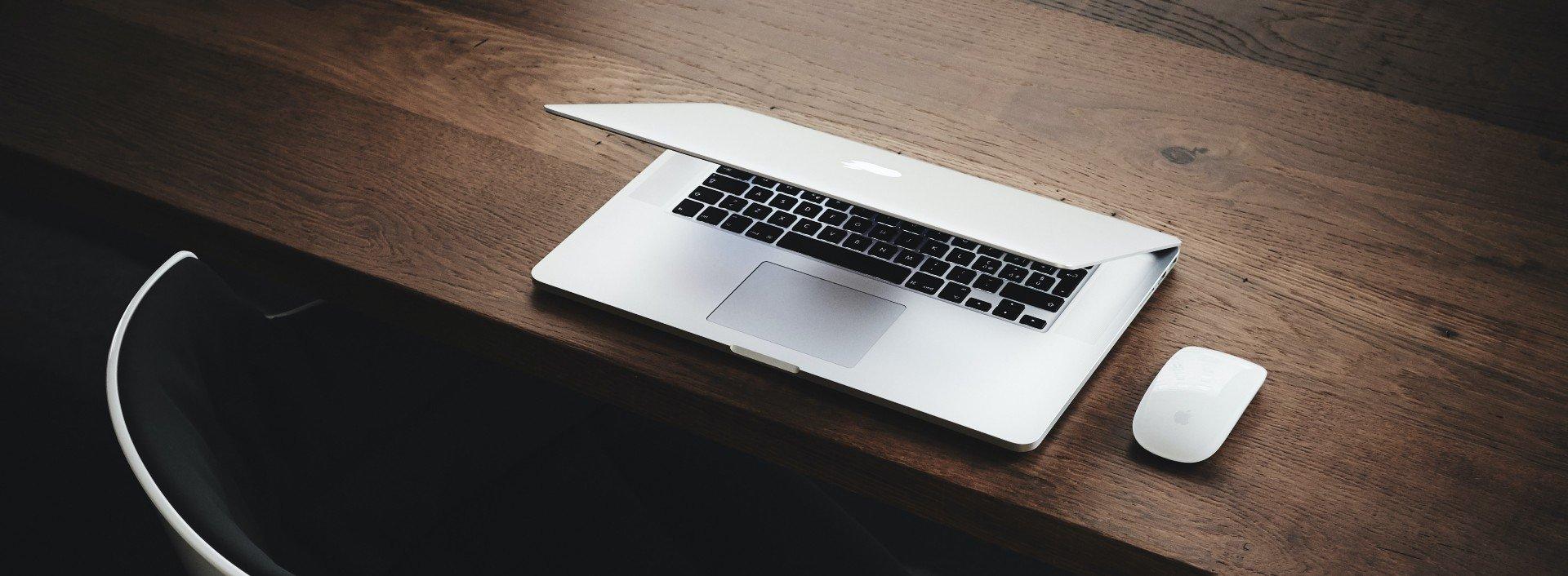 Auszeit von der Arbeit: Auf einem braunen Holztisch liegt ein halb zugeklappter Laptop.